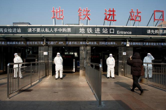 Contrôle de la température corporelle à l'entrée du métro de Pékin, le 25 janvier.