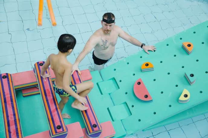 Adam (7 ans) et son maître-nageur, Jacky Guillot, lors de la séance de natation organisée au centre aquatique de Neuilly-sur-Seine (Hauts-de-Seine).