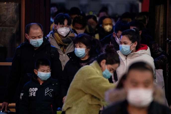 Des usagers des transports en commun portant des masques de protection, dans une gare de Pékin, le 29 janvier.