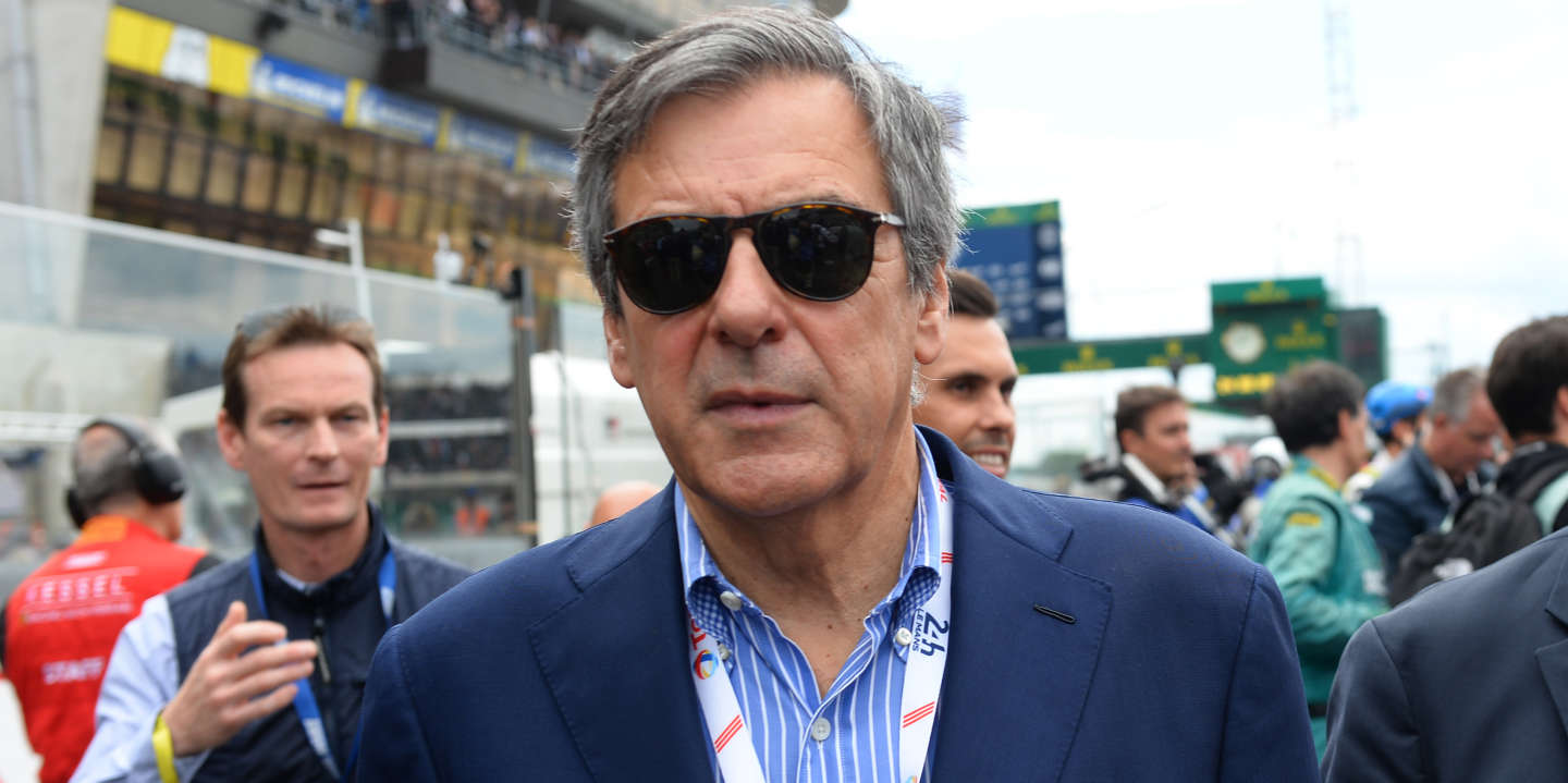 Former French Prime Minister Francois Fillon (L) walks with Louis Derboulle administrator of Automobile club de l'Ouest (R) in the grid prior to the 87th edition of the Le Mans 24 Hours endurance race, in Le Mans, northwestern France, on June 15, 2019. - ( (Photo by JEAN-FRANCOIS MONIER / AFP)