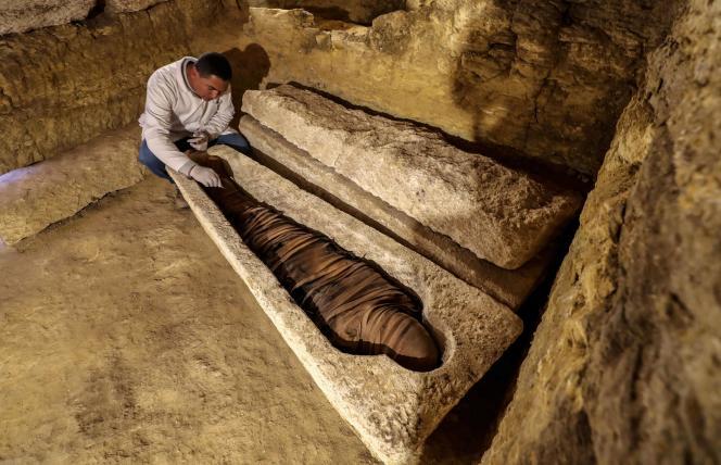 Le 30 janvier, un archéologue égyptien examine une momie découverte dans un sarcophage en calcaire à 300 km au sud du Caire.