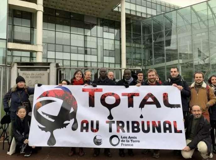 Des représentants des Amis de la Terre et de Survie manifestent contre Total devant le tribunal de grande instance de Nanterre, le 12 décembre 2019.