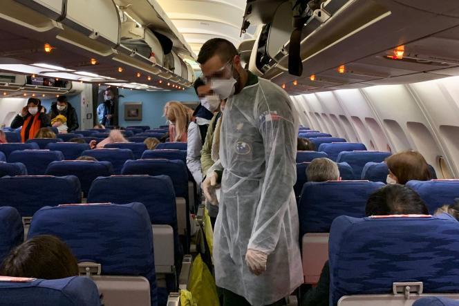 Des citoyens français à bord d'un avion d'évacuation à destination du sud-est de la France, avant le départ de l'aéroport de Wuhan, en Chine, dans la nuit du30 au 31janvier.