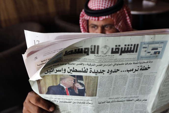 Dans un café à Djeddah, le 29 janvier, un Saoudien lit le quotidien «Asharq Al-Awsat»qui fait sa « une» sur Donald Trump.