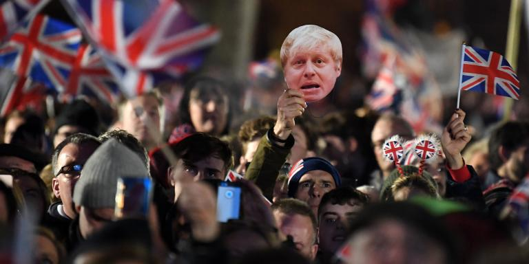 Brexit supporters wave Union flags ans a mask of Britain's Prime Minister Boris Johnson as the time reaches 11 O'Clock, in Parliament Square, venue for the Leave Means Leave Brexit Celebration in central London on January 31, 2020, the moment that the UK formally leaft the European Union. Brexit supporters gathered outside parliament on Friday to cheer Britain's departure from the European Union following three years of epic political drama -- but for others there were only tears. After 47 years in the European fold, the country leaves the EU at 11:00pm (2300 GMT) on Friday, with a handful of the most enthusiastic supporters gathering opposite the Houses of Parliament 12 hours before the final countdown. / AFP / DANIEL LEAL-OLIVAS