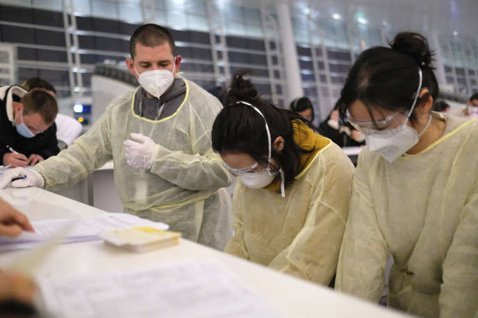 Des voyageurs, portant masque et vêtements de protection, remplissent les formalités d'immigration, à l'aéroport de Wuhan, le 1er février.
