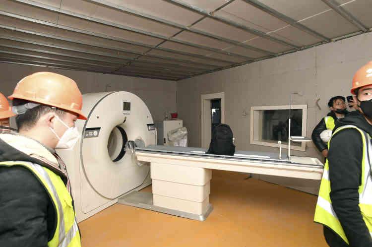 Des ouvriers finissent d'installer un scanner à tomographie dans le nouvel hôpital.