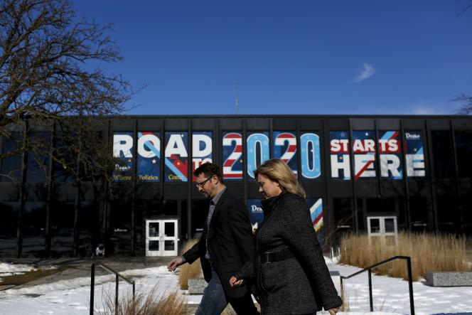 Des passants devant une affiche « La route pour 2020 commence ici», à Des Moines (Iowa), le 2 février.