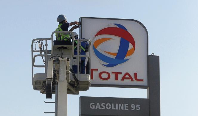 Des ouvriers installent le logo du géant pétrolier français Total dans une station-service du Caire, en octobre 2016.