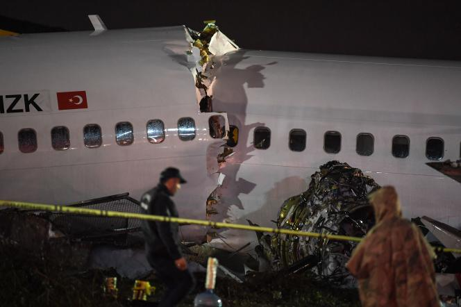 A turkish soldier stand guard as rescuers work at the crash of a Pegasus Airlines Boeing 737 airplane, after it skidded off the runway upon landing at Sabiha Gokcen airport in Istanbul on February 5, 2020. The plane carrying 171 passengers from the Aegean port city of Izmir split into three after landing in rough weather. Officials said no-one had lost their lives in the accident, but dozens of people were injured. / AFP / Ozan KOSE