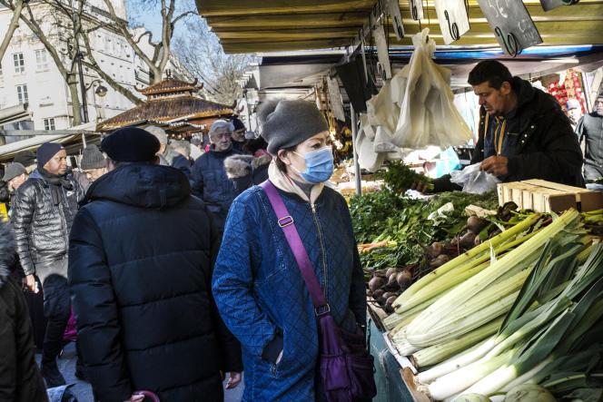 Une femme portant un masque de protection fait son marché dans le quartier de Belleville, à Paris, le 7 février.