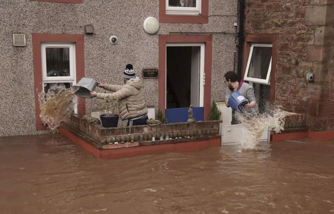 Deux hommes écopent l'eau à l'entrée de leur maison touchée par les innondations, à Appleby-in-Westmorland, dans le nord de l'Angleterre.