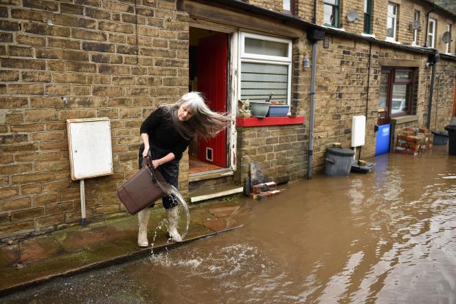 Une femme vide l'eau de sa maison, touchée par les inondations provoquées par la tempête Ciara, à Mytholmroyd, au Royaume-Uni, le 9 février.
