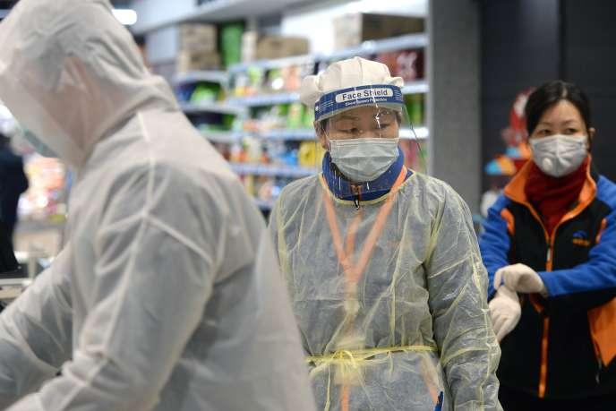 Un membre du personnel d'un supermarché portant un masque de protection et une combinaison à Wuhan, le 10 février.