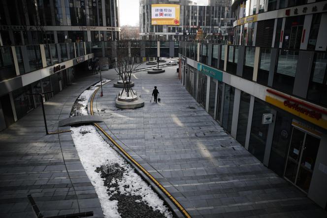 Un technicien de surface traverse l'enceinte déserte d'un immeuble de bureaux à Pékin, le 10 février.