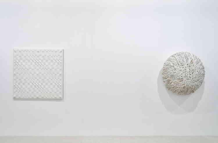 «Cette toile monochrome, au motif en relief obtenu par des clous positionnés au dos de la toile, située à gauche de l'image, est emblématique du travail de l'artiste. Ainsi, la lumière et l'ombre –et l'espace qu'elles génèrent– sont contenues dans l'œuvre elle-même et transforment la toile en une membrane vivante.»