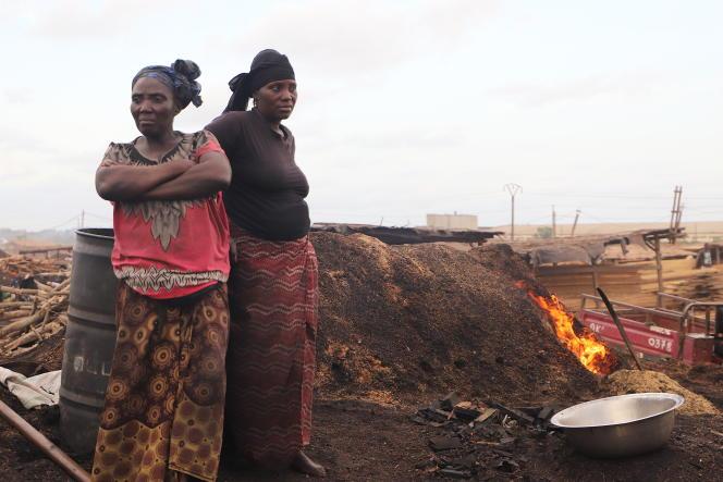 Awa Diabaté (à droite) et son amie Fanta près d'un four à charbon de bois, à l'entrée de San Pedro, en février 2020.