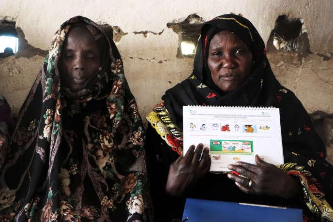 Deux matrones montrent le dictionnaire illustré qu'elle ont obtenu en formation, au centre de santé de Kékédina,dans l'ouest tchadien,le 29 janvier 2020.