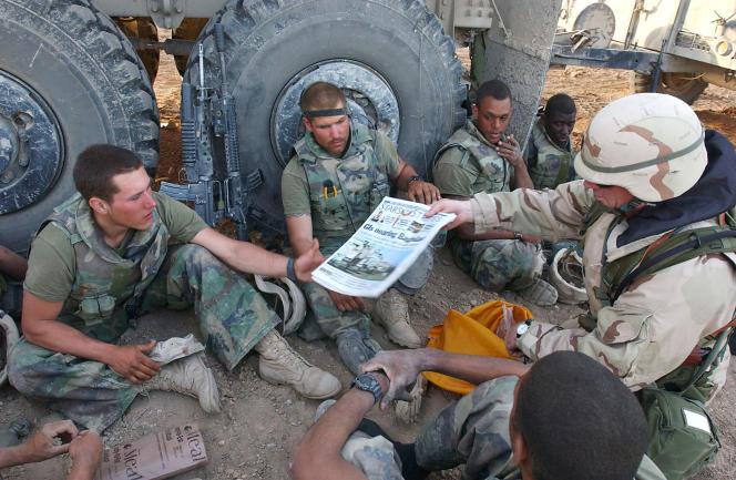 Distribution d'exemplaires de «Stars and Stripes» aux Marines de la Force opérationnelle Tarawa, déployée en Irak, en 2003.