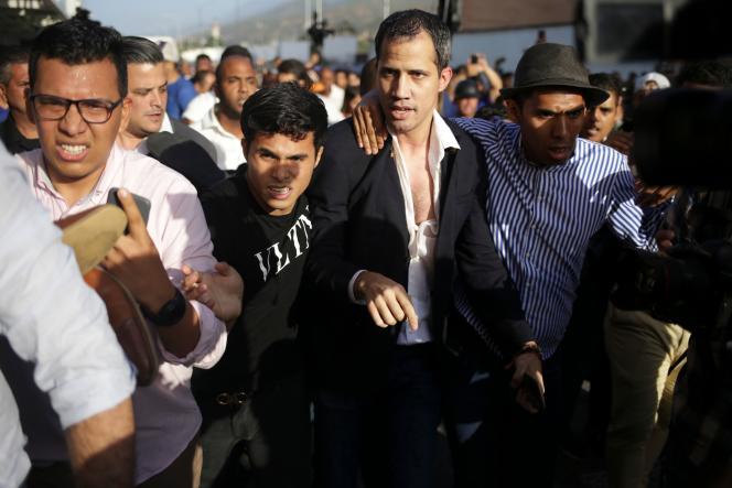 Le chef de l'opposition vénézuélienne, Juan Guaido, escorté vers son véhicule après son arrivée à l'aéroport international deMaiquetia, le 11 février.