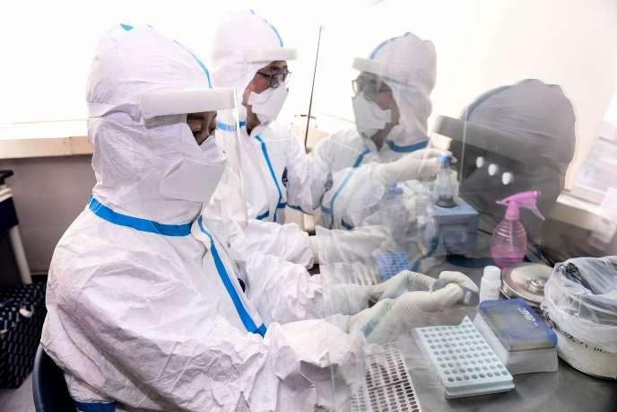 Des techniciens de laboratoire testent des échantillons au COVID-19, à Shenyang, au nord-est de la Chine, le 12février.