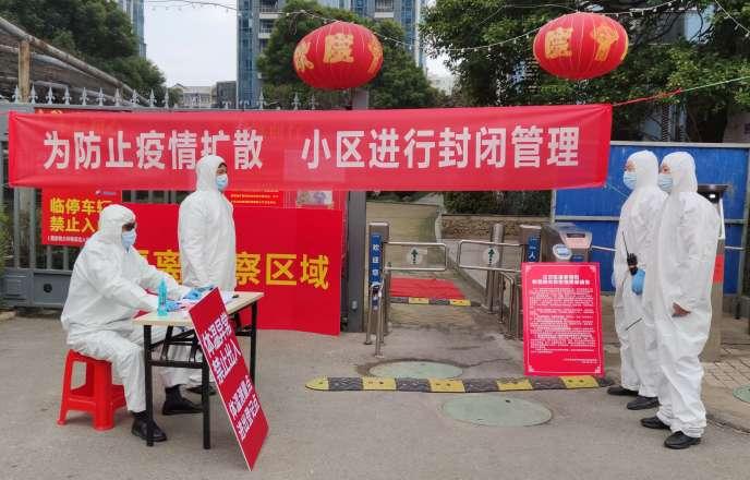 A Wuhan, un point de contrôle de température à l'entrée d'un complexe résidentiel, le 13 février.