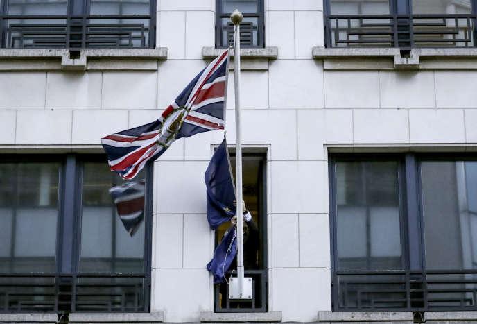 Un membre du protocole enlève le drapeau de l'Union européenne devant l'ancienne représentation permanente du Royaume-Uni à Bruxelles, le 31 janvier.
