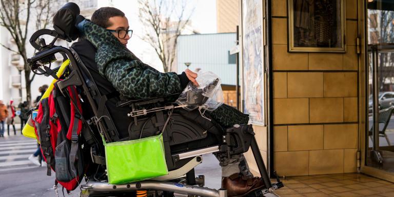 Paris, France, le 13 Fevrier 2020 : Reportage avec Brice Laemle. Alexandre et Xavier quittent les locaux de l'APF pour aller manger une pizza dans le quartier. Sur l'image Alexandre est devant le café du coin de la rue, inaccessible pour lui a cause de la petite marche qui l'empêche de rentrer avec son fauteuil.