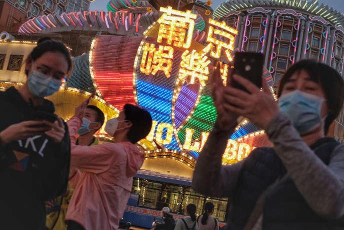 Des touristes portant des masques prennent des photos devant le casino Lisboa, à Macao, le 23 janvier.