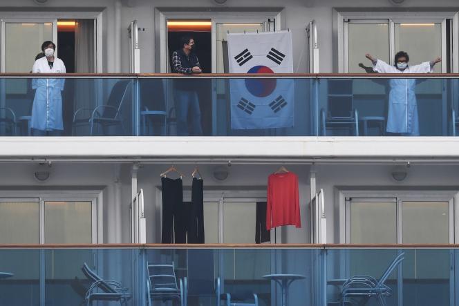 Des passagers du «Diamond Princess» en quarantaine sortent sur leurs balcons, le 14 février 2020.