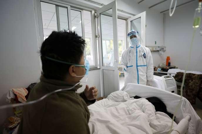 Un employé médical assiste un patient dans un service isolé de l'hôpital de Wuhan, le 13 février.