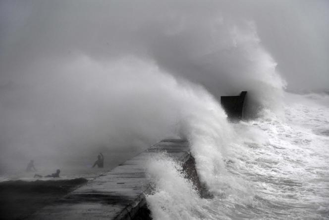 Des surfeurs se baignent durant la tempête Dennis, àPlobannalec-Lesconil dimanche 16 février.