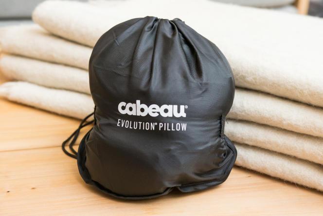 Le coussin Cabeau se réduit en un tiers de sa taille dans son étui de transport, sanglé par une bande Velcro.