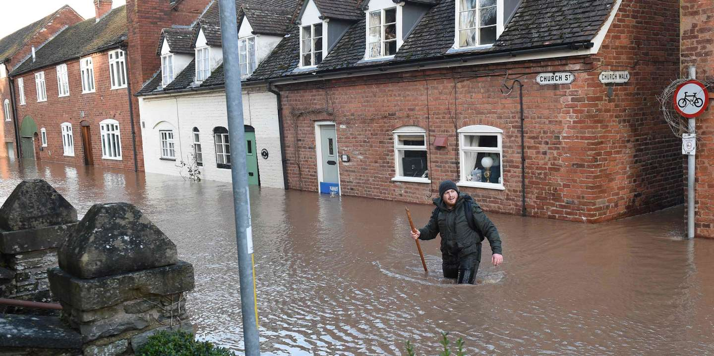 A man wades through in flood water as he passes houses in Church Street in Tenbury Wells, after the River Teme burst its banks in western England, on February 16, 2020, after Storm Dennis caused flooding across large swathes of Britain.  A man died after falling into a river on Sunday as Storm Dennis swept across Britain with the army drafted in to help deal with heavy flooding and high winds. / AFP / Oli SCARFF