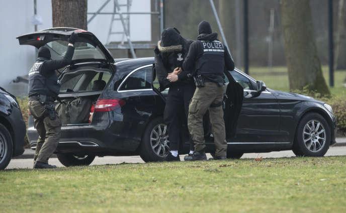 Des officiers de police allemands escortent l'un des douze suspects au tribunal de Karlsruhe, en Allemagne, le 15 février.