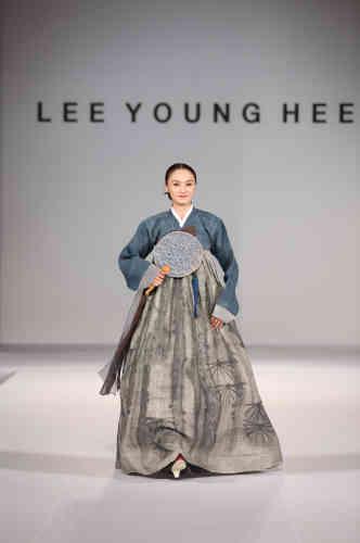 «Lee Young-hee met en valeur les arts et traditions de la Corée : ici, la peinture traditionnelle à l'encre est à l'honneur, avec le motif du pin, symbole de bon augure associé à la longévité, qui se déploie librement sur la jupe.»