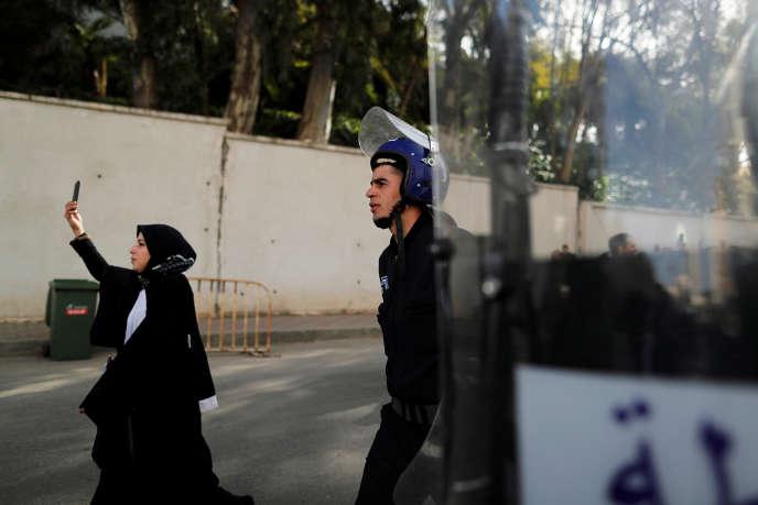 Une avocate brandit son téléphone portable près d'un policier lors d'une manifestation anti-gouvernementale à Alger, le 7mars 2019.
