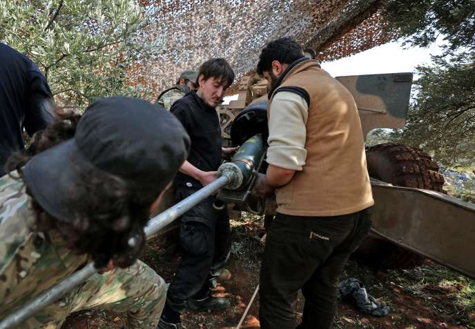 Des combattants syriens soutenus par la Turquie chargent un obus près du village d'al-Nayrab, près de la ville d'Idlib (Syrie), au milieu d'affrontements avec les forces gouvernementales, le 20 février.
