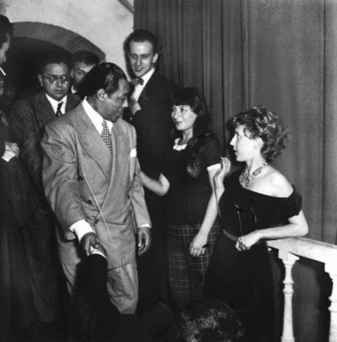 Le pianiste et compositeur de jazz américain Duke Ellington est félicité par, de gauche à droite, Boris Vian, Juliette Gréco et Anne-Marie Cazalis au Club Saint-Germain-des-Prés, à Paris, à l'occasion d'un gala organisé en son honneur, le 19 juillet 1948. Derrière eux, le pianiste Jacques Diéval.