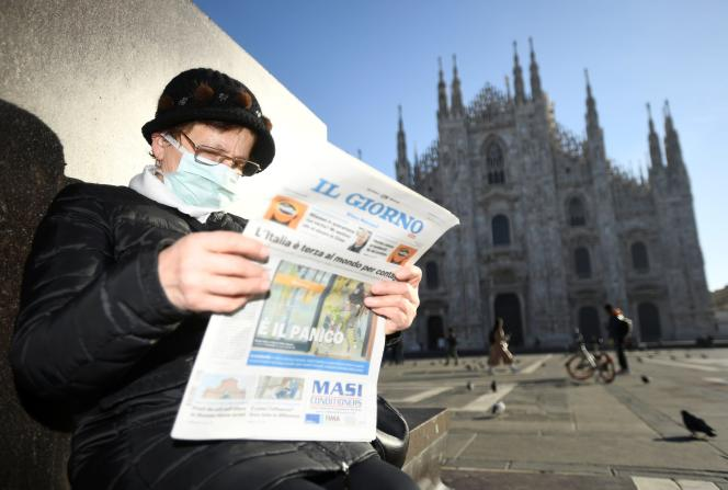 Une femme lit le journal devant la cathédrale de Milan, lundi 24 février.