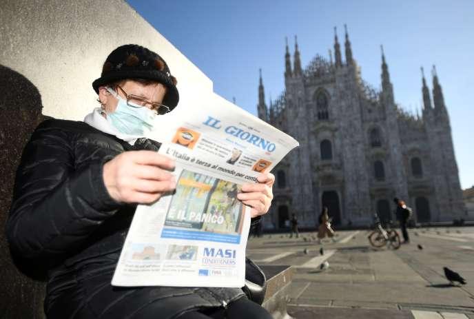 Un homme lit le journal devant la cathédrale de Milan, lundi 24 février.