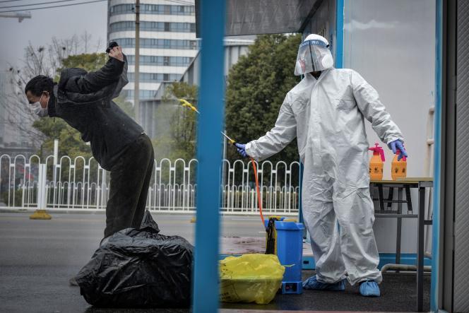 Un homme qui s'est remis du SARS-CoV-2, virus responsable de Covid-19, estdésinfecté par un membre du personnel médical avant de quitter l'hôpital de Wuhan, dans la province centrale du Hubei, en Chine, le 22février2020.