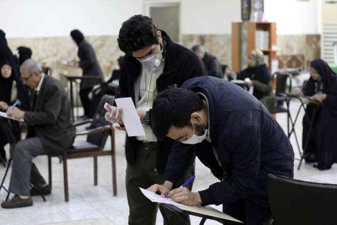 Des électeurs iraniens, protégés par un masque, remplissent leur bulletin de vote lors des élections législatives, à Téhéran, le 21 février.