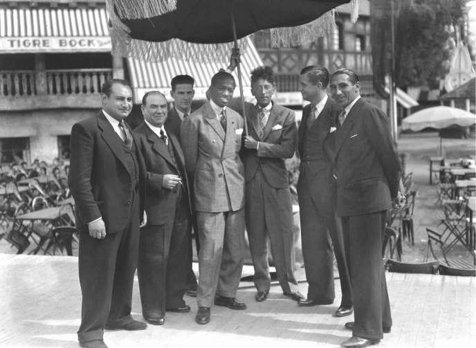 Au centre, Panama Al Brown (1902-1951), boxeur panaméen, en compagnie de Jean Cocteau (1889-1963), écrivain et cinéaste français.