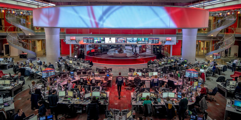 UK. London. 21st February 2020. The BBC Newsroom. In the background, the BBC news is broadcasting live, in the foreground are the journalists and editors who work on the programme. Andrew Testa for Le Monde