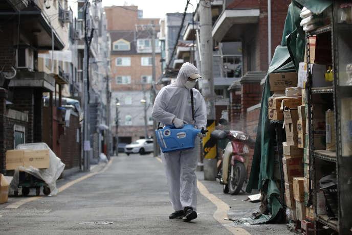 Un employé en combinaison désinfecte un marché par précaution, le 26 février àSéoul, en Corée du Sud.