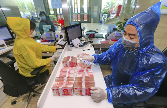 Un employé de banque désinfecte des billets, à Suining, dans la province du Sichuan, le 26 février.