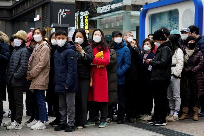 Des Sud-Coréens patientent devant un magasin pour acheter des masques, le 28 février, à Séoul.