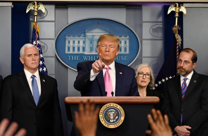 Donald Trump entouré de son vice-président, Mike Pence, et de son secrétaire à la santé, Alexander Azar, à la Maison Blanche, à Washington, le 26 février.