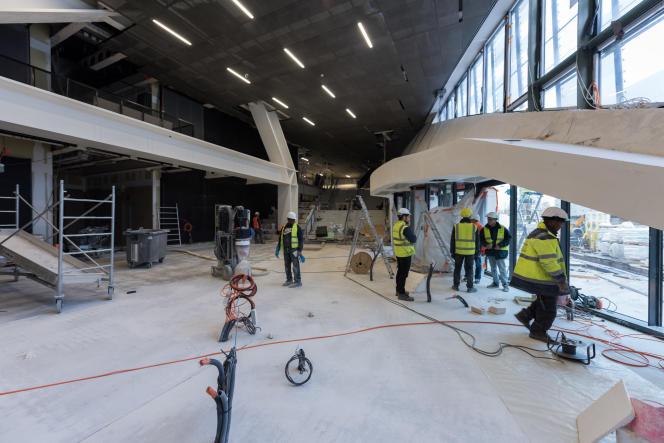 Des ouvriers travaillent dans le hall d'entrée du futur siège du Groupe Le Monde, à Paris.
